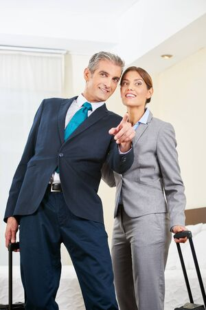 Businesspeople with suitcase as a couple in a hotel room