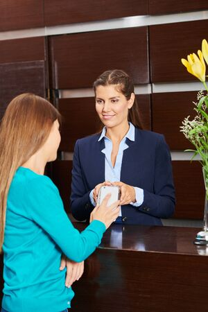 Woman paying with smartphone at hotel reception during check-out