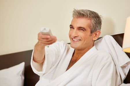 Elderly man watching TV in hotel room while holding the remote control