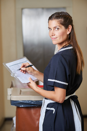 Hotel maid with quality checklist during housekeeping