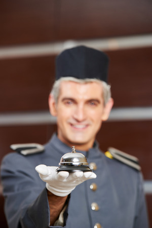 Hotel bell on hand of concierge as service symbol