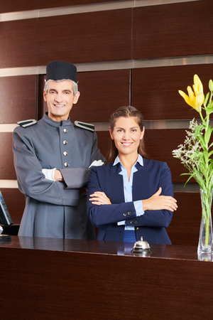 Page and receptionist at hotel reception smiling as a team