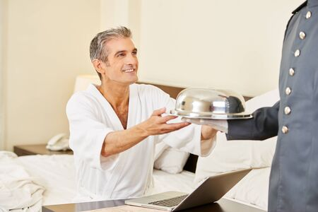 Room service bringing food to guest with laptop in a hotel room Stock Photo