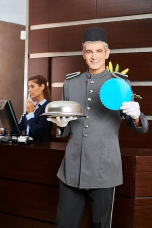 Concierge in hotel at reception with a badge and food cloche