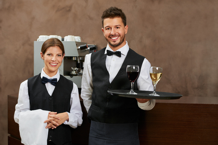 Waiter and waitress serving drinks in a hotel restaurant Stock Photo