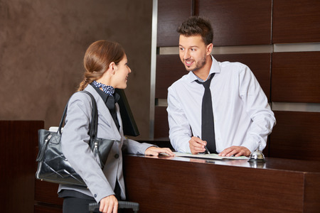 Hotel concierge offering tipps on city map to female guest Stock Photo