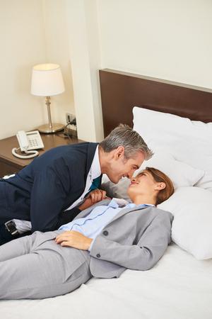 Twee mensen uit het bedrijfsleven een affaire in een hotelkamer tijdens een zakenreis Stockfoto