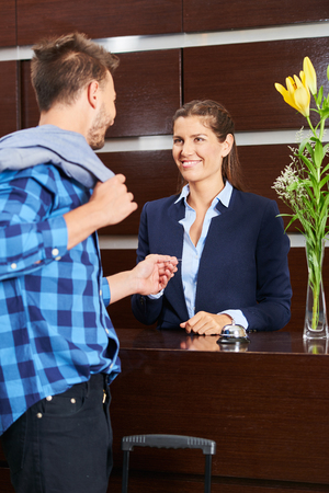Man giving key card to hotel receptionist during check-out