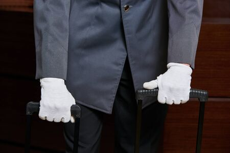 Concierge with white gloves and suitcases in a hotel