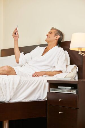 Man in hotel room reading text message on his smartphone Stock Photo