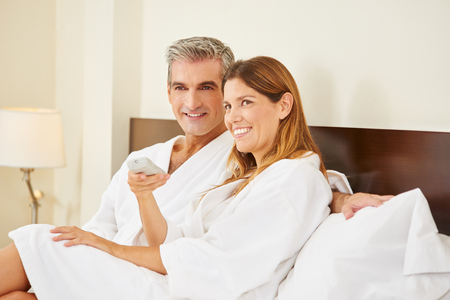 Happy couple watching TV in hotel room during holiday