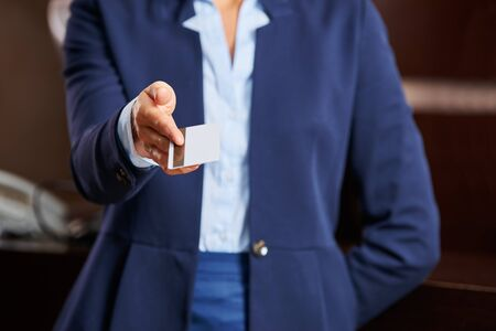 Hand of concierge offering a key card to hotel guest