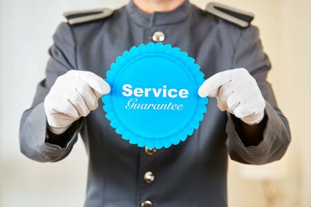 Hotel page holding service guarantee badge in his hands