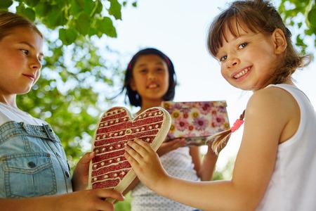 Children wish happy birthday to girl with gift Stock Photo