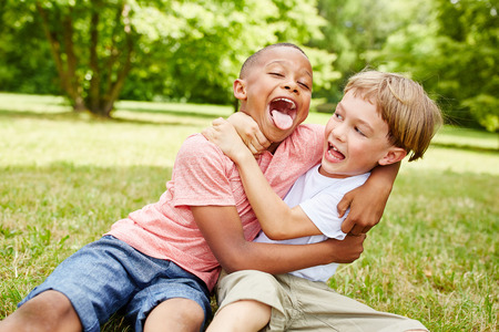 Two boys have fun in the park and wrestle while laughing