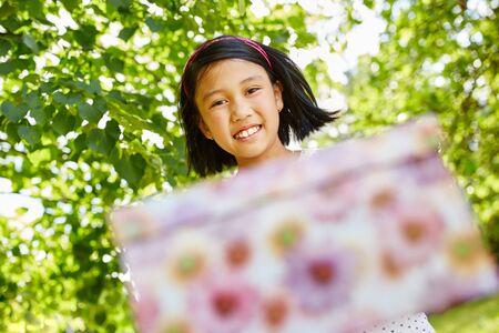 Girl donates birthday present with joy as a surprise Stock Photo