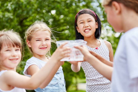 Three girls clinking their glasses of water at birthday party