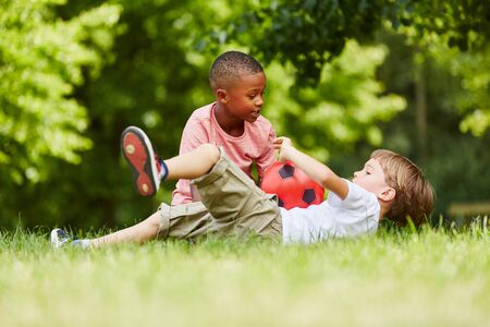Two boys playing soccer together in the park in summer Stock Photo