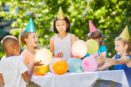 Many kids celebrate birthday together with balloons and party hats Фото со стока