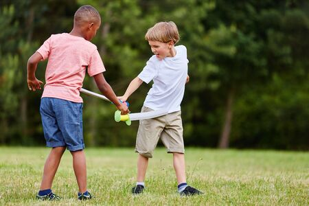 Two children fighting as pirates or knights with swords