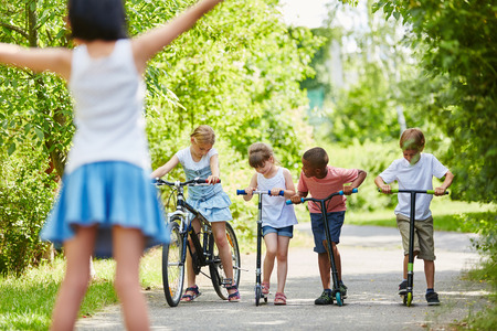 Group of kids ready for competition in the park with bike and scooters Stock Photo
