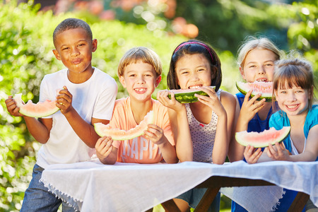 Childrean eating healthy melon as friends in summer in interracial community