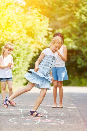 Children play hopscotch in summer in kindergarten