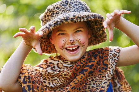 Creative child playing in leopard costume in fantasy face paiting class