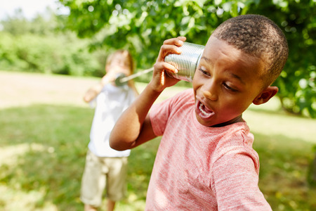African boy calling friend with tin can telephone in summer in the park Stock Photo