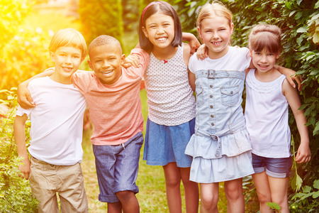 clique: Group of children smiling as friends together in summer in garden