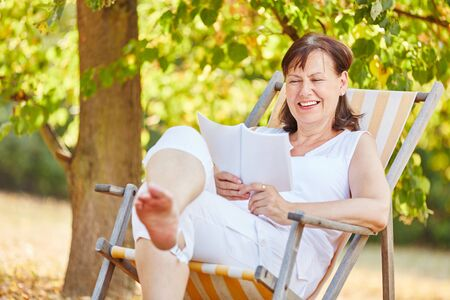 senior woman: Relaxed senior woman reading on a deck chair in summer in the gardent