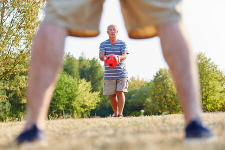 communication occupation: Two active senior men playing soccer in the park Stock Photo