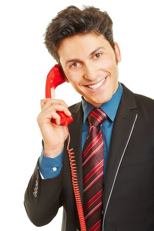 telephone call: Smiling business man making phone call with a red telephone
