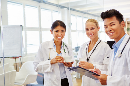 medical doctors: Interracial team of doctors in medical school studying in apprenticeship workshop Stock Photo