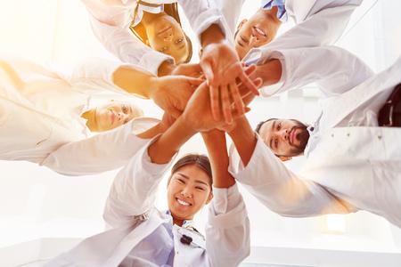 Veel gelukkige artsen stapelen elkaar samen als team voor motivatie Stockfoto