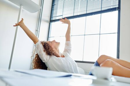 Businesswoman in office stretching her arms and relaxing Фото со стока