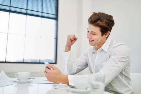 Businessman celebrates SMS in smartphone with fist up