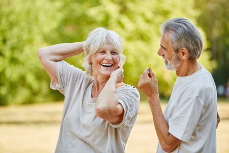 Old man gives a flower to senior smiling woman in the nature