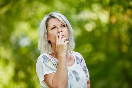 Hogere vrouw die een sigaret roken voor het ontspannen in de zomer