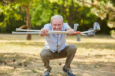 Old man with vitality and crutches in rehab having fun Stock Photo