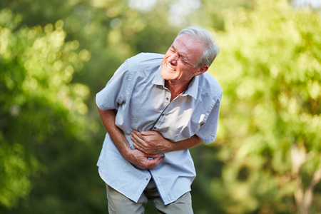 convulsion: Old man with stomach ache toching his stomach in the nature