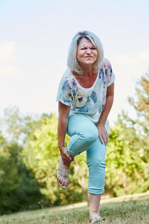 Alte Frau mit verstauchten Fuß hat Schmerzen in der Natur Standard-Bild - 73082686