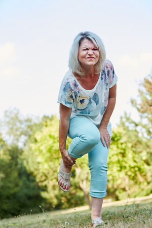 Old woman with sprained foot has pain in the nature
