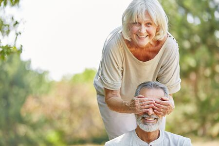 Senior woman covers her husbands eyes from the back in the nature Stock Photo