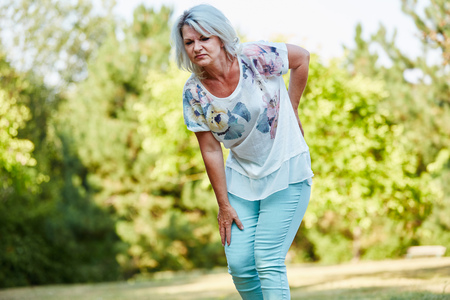 spinal disks: Old woman with lumbago pain while walking in the nature Stock Photo
