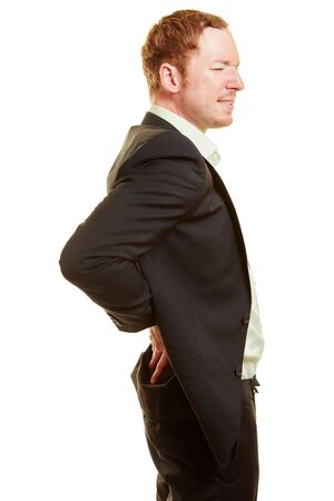Man with back pain holding his hands on his back in business clothing