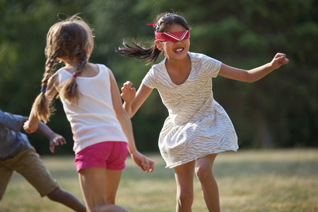 buff: Happy children playing blind mans buff in summer at a birthday party Stock Photo