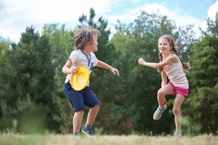 Girl and boy playing frisbee in the summer and having fun
