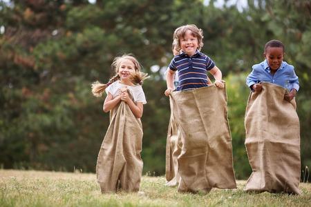 saltar: Niños que compiten en la carrera del saco y que se divierten Foto de archivo