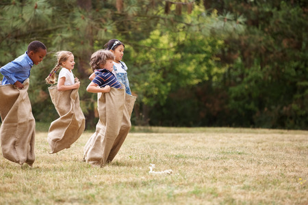 Kinderen in een zakrace concurreren met elkaar in de zomer